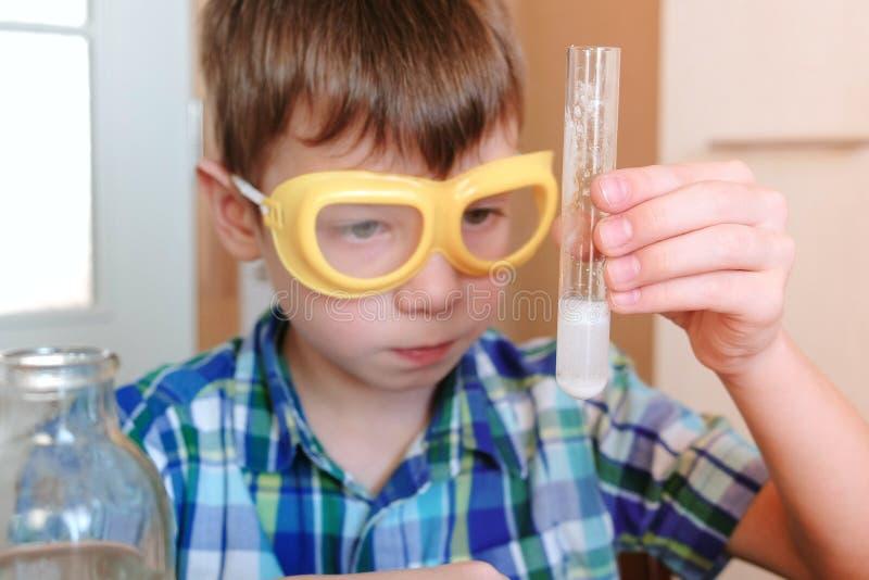 Eksperymenty na chemii w domu Chłopiec jest przyglądającym Chemicznym reakcją z uwolnieniem gaz w próbnej tubce w rękach obrazy stock