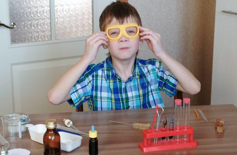 Eksperymenty na chemii w domu Chłopiec kładzenie na zbawczych żółtych gogle siedzi przy stołem obraz royalty free