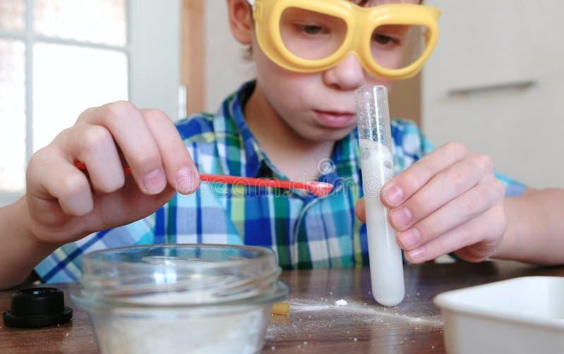Eksperymenty na chemii w domu Chemiczna reakcja z uwolnieniem gaz w próbnej tubce w chłopiec, s ręki zdjęcie stock