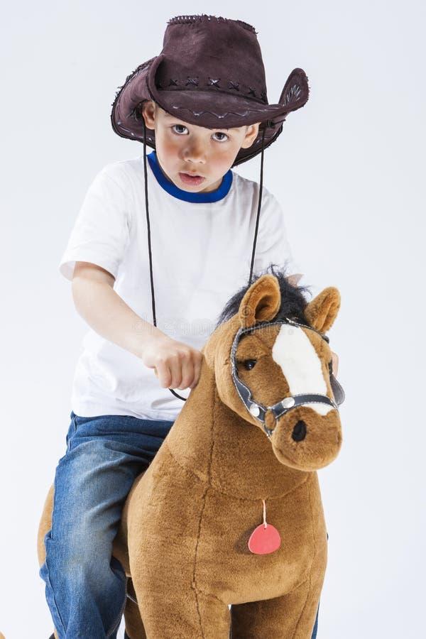 Ekspresyjna chłopiec w Kowbojskiej odzieży Pozuje Z Symbolicznym Pluszowym koniem obraz stock