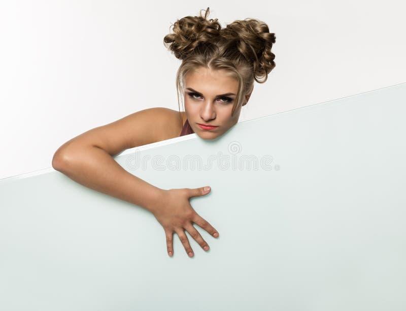 Ekspresyjna dziewczyny pozycja behind i opierający na billboardzie białym pustym plakacie lub, kopii przestrzeń dla twój teksta fotografia stock