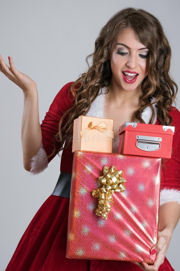 Ekstatische Sankt-Frau tragende Weihnachtsgeschenke, die unten schauen lizenzfreies stockbild