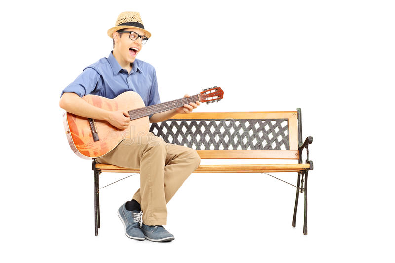 Ekstatischer junger auf Bank sitzender und singender Gitarrist lizenzfreie stockfotos