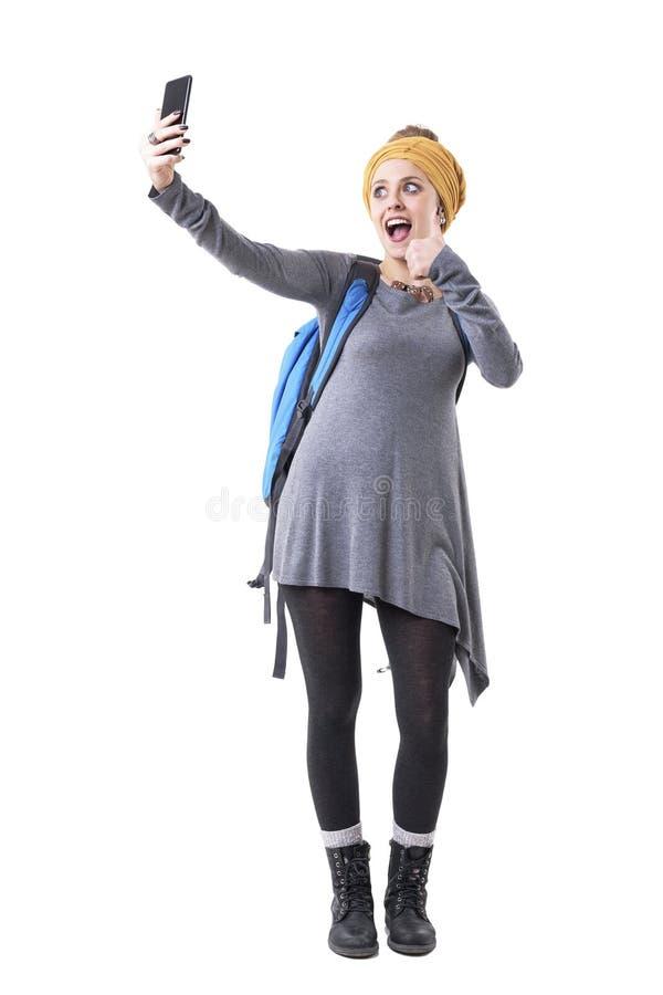 Ekstatyczna rozochocona młoda turystyczna kobieta bierze selfie z aprobatami gestykuluje zdjęcia stock