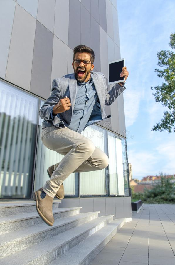 Ekstatyczny biznesmen skacze przed budynkiem biurowym fotografia stock