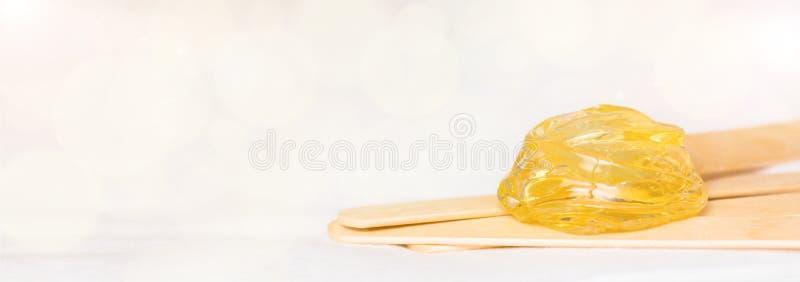 Ekstra szeroki sztandaru tło z cukrowym miodem dla włosy usuwać i drewnianymi nawoskuje szpachelka kijami pasty lub wosku - de obrazy stock