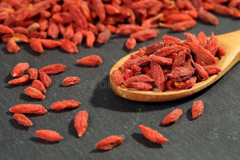 Ekstremum zamknięty w górę wysuszonych organicznie goji jagodowych owoc wolfberries w drewnianej łyżce na czarnym kamieniu ukazuj obrazy royalty free