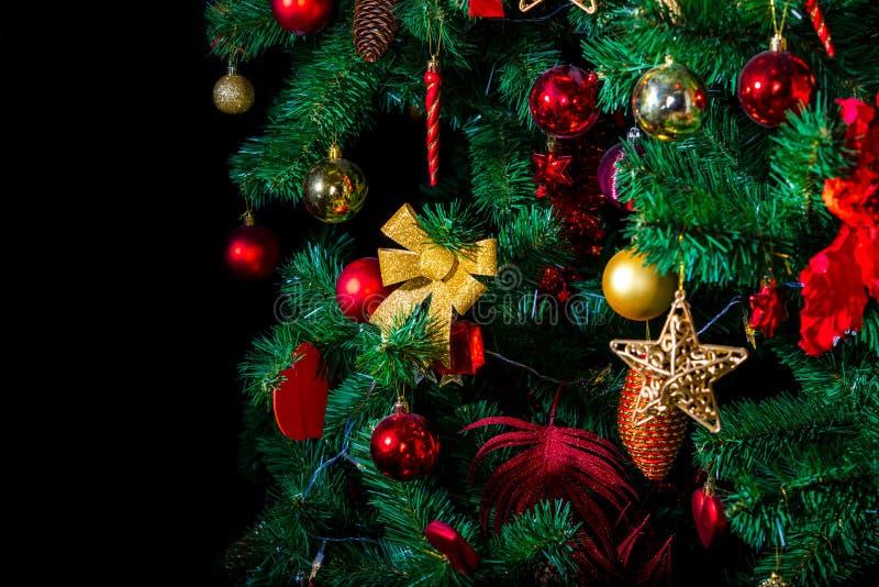 Elégant décor de Noël, éco-arbre vert en plastique décoré de nombreux jouets colorés d'or et de rouge, archet, étoile et balles photographie stock libre de droits