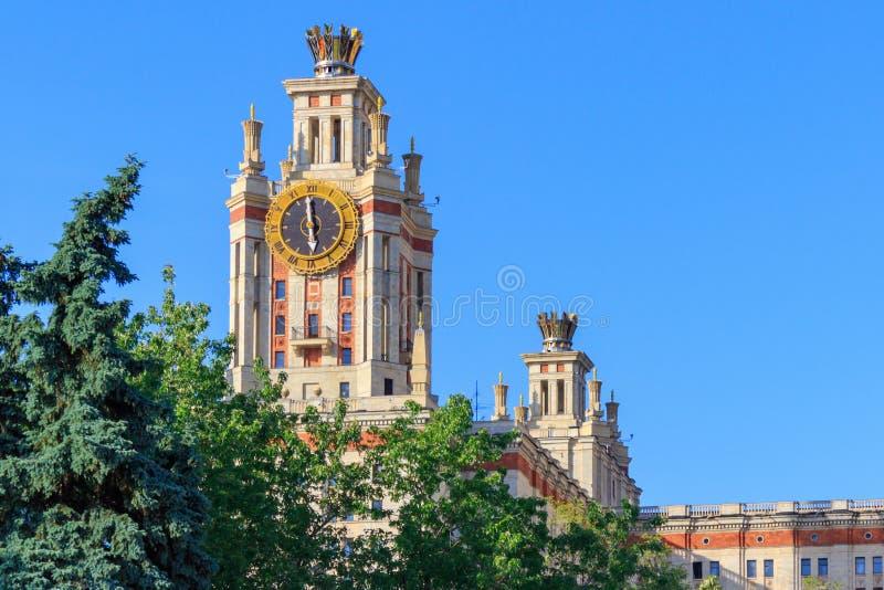 Elévese con el reloj de la universidad de estado de Lomonosov Moscú MSU contra árboles verdes por la tarde soleada del verano fotos de archivo