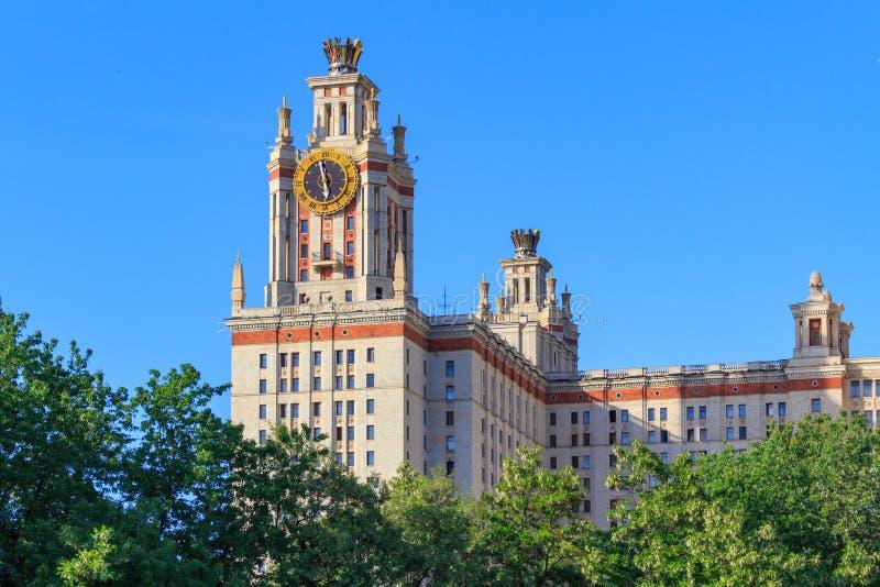 Elévese con el reloj de la universidad de estado de Lomonosov Moscú MSU contra árboles verdes y el cielo azul fotos de archivo