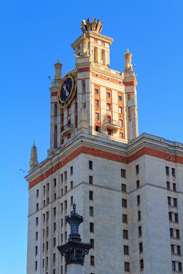Elévese con el reloj de la universidad de estado de Lomonosov Moscú MSU contra el cielo azul por la tarde soleada del verano fotografía de archivo