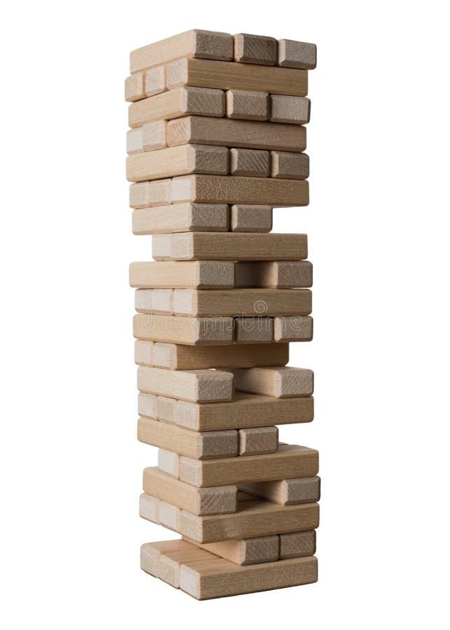 Elévese de los bloques de madera para el juego del jenga aislado en el fondo blanco Concepto de riesgo y de estrategia para guard imagen de archivo libre de regalías
