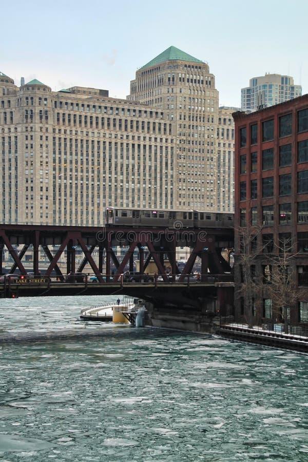 El火车移动在有冰大块的冻芝加哥河 图库摄影