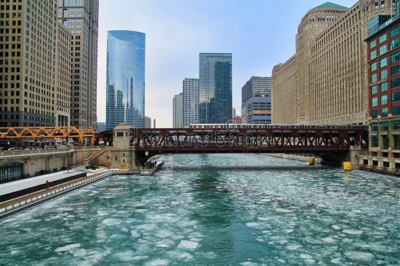 El火车移动在有冰大块的蓝色和冻芝加哥河 库存照片