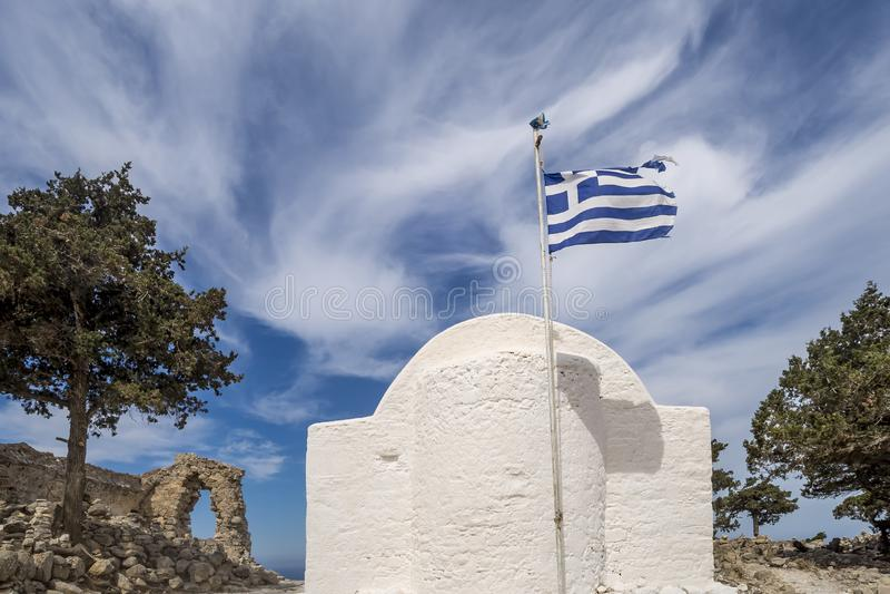 El ábside de una iglesia griega típica con la bandera en el viento entre las ruinas del castillo medieval Monolithos, Rodas, Grec fotografía de archivo