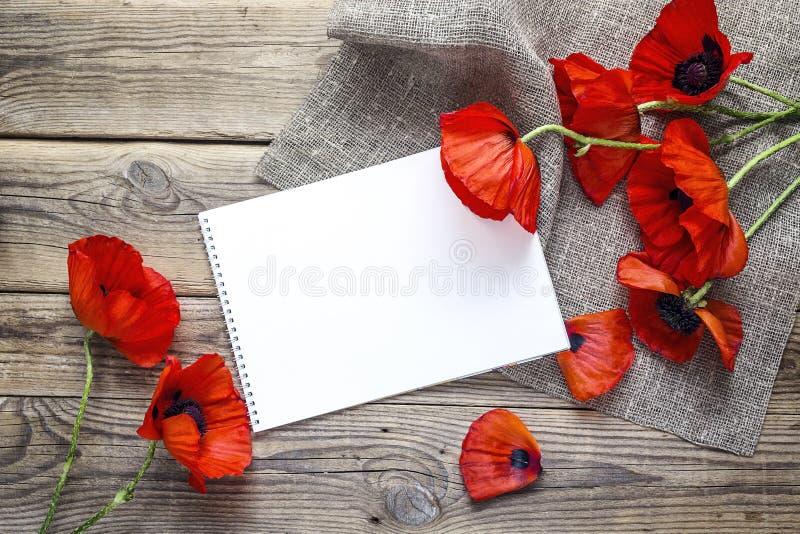 El álbum del arte y las amapolas rojas florece con la servilleta de la arpillera en t de madera imagen de archivo