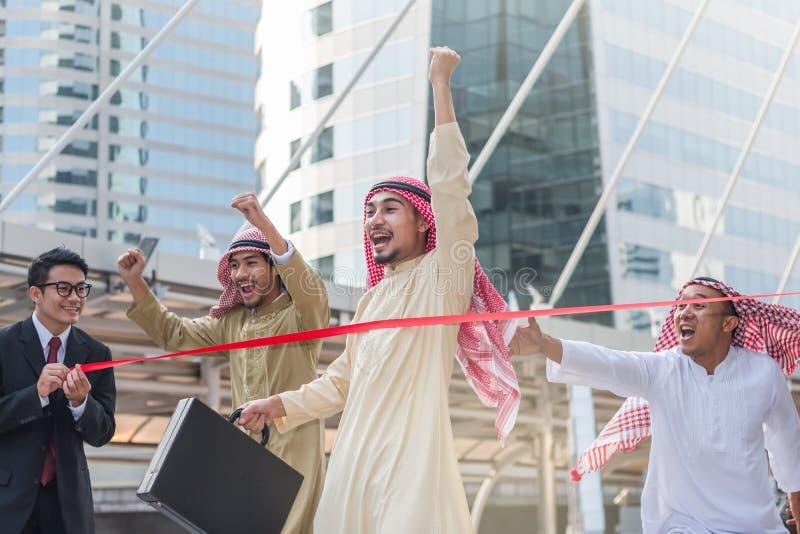 El árabe corre para ir a la línea de meta y su competidor está detrás fotos de archivo libres de regalías