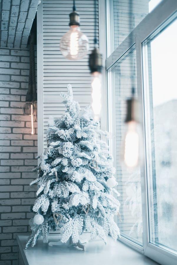 El árbol de navidad en la nieve está en la ventana imágenes de archivo libres de regalías