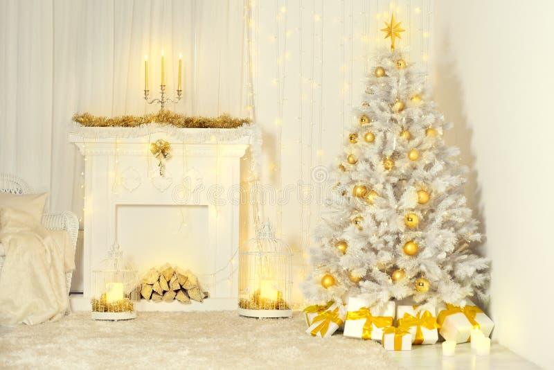 El árbol de navidad y la chimenea, color oro adornaron el sitio interior fotografía de archivo