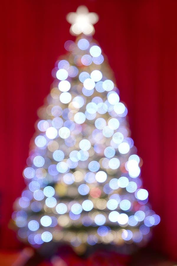 El árbol de navidad y las luces desenfocado empañaron bolas y decoraciones con malla contra colorido brillante de las cortinas ro foto de archivo