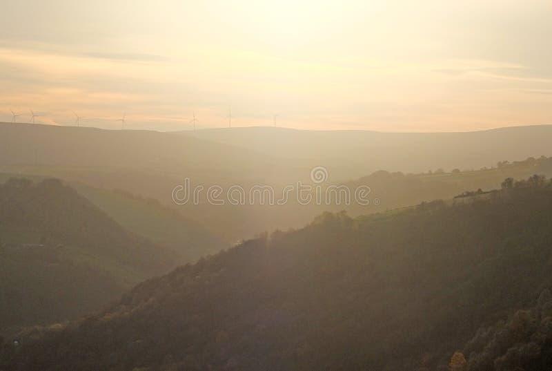 El árbol suave de la ladera cubrió paisaje del valle borroso por la niebla en la puesta del sol que brillaba intensamente un colo fotos de archivo