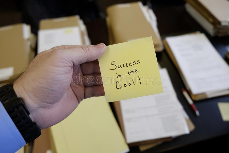 El éxito de trabajo de Desk Files Folder del hombre de negocios disponible pegajoso de la nota es la meta foto de archivo