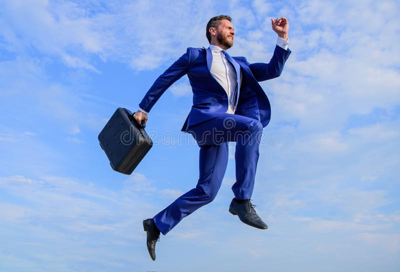 El éxito en negocio exige esfuerzos sobrenaturales Hombre de negocios con el salto de la cartera alto en el movimiento adelante s imagen de archivo libre de regalías