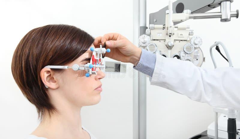 El óptico con el marco de ensayo, doctor del optometrista examina vista imágenes de archivo libres de regalías