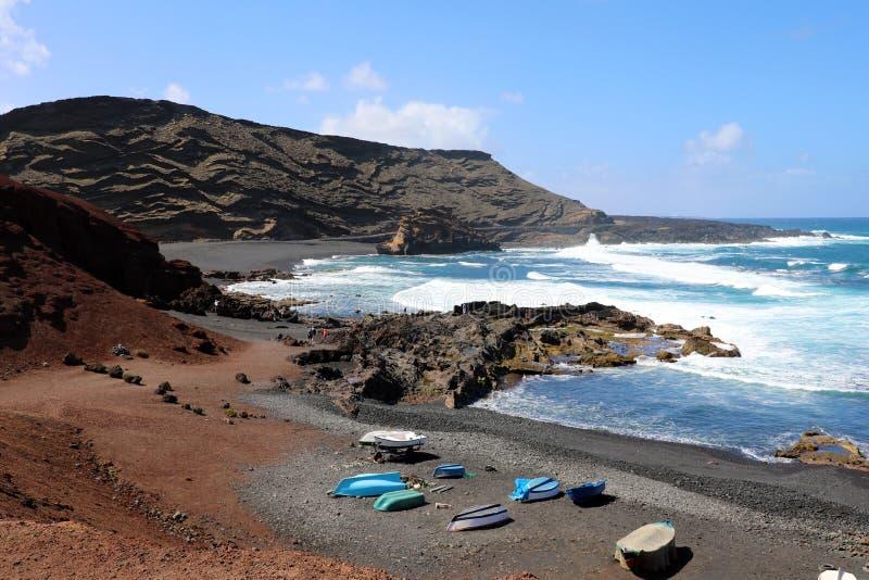 El Golfo海湾激动人心的景色与小船的:红色地面,蓝色海和黑铺沙与在背景,兰萨罗特岛的火山的山 免版税库存图片