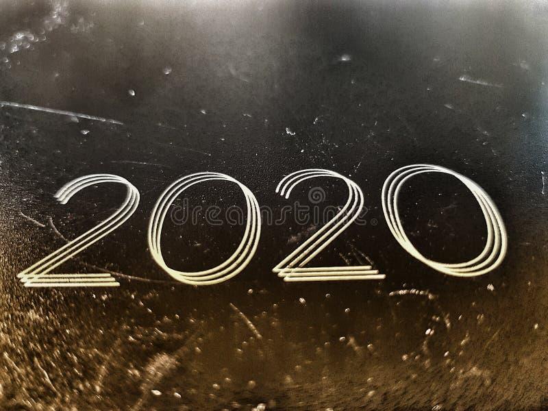 El año 2020 estampado en una vieja foto de un cuaderno de cuero desgastado y marcado vista angled imágenes de archivo libres de regalías