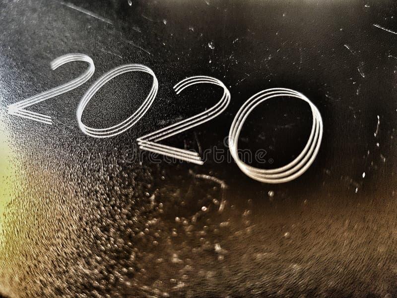 El año 2020 estampado en una vieja foto de un cuaderno de cuero desgastado y marcado vista angled foto de archivo