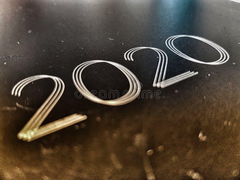El año 2020 estampado en una vieja foto de un cuaderno de cuero desgastado y marcado vista angled imagen de archivo