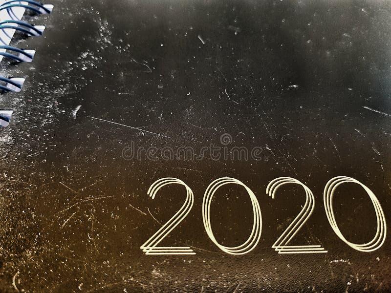El año 2020 estampado en una vieja foto de un cuaderno de cuero desgastado y marcado vista angled imagenes de archivo
