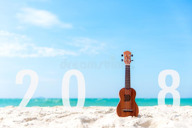 El Año Nuevo 2018 con el ukelele de la guitarra para se relaja en el fondo de la playa hermosa y del cielo azul para la estación  imagen de archivo