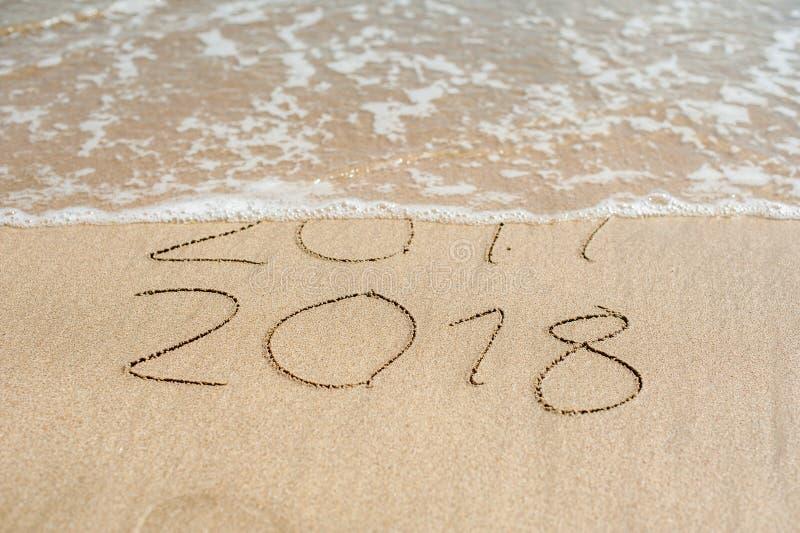 El Año Nuevo 2018 es concepto que viene - la inscripción 2017 y 2018 en una arena de la playa, la onda casi está cubriendo los dí imágenes de archivo libres de regalías