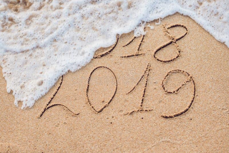 El Año Nuevo 2019 es concepto que viene - la inscripción 2018 y 2019 en una arena de la playa, la onda casi está cubriendo los dí imagenes de archivo