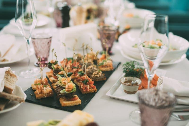 El abastecimiento mantiene el fondo con bocados y vidrios de vino en contador del camarero en restaurante imágenes de archivo libres de regalías