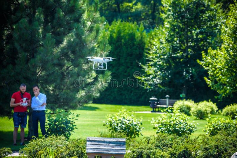 El abejón compacto asoma delante de dos hombres del inconformista El helicóptero del patio vuela cerca de piloto Innov de explora fotografía de archivo libre de regalías