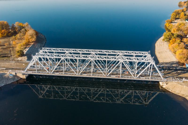 El abejón de la visión aérea tiró del puente de acero del ferrocarril que cruzaba el río azul grande, transporte del tren fotos de archivo libres de regalías