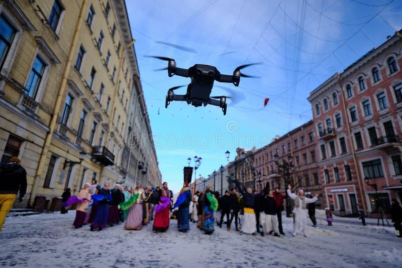 El abej?n vuela bajo en el centro de la ciudad y lleva la foto y el v?deo que filma en un festival de la ciudad Color negro imagen de archivo libre de regalías