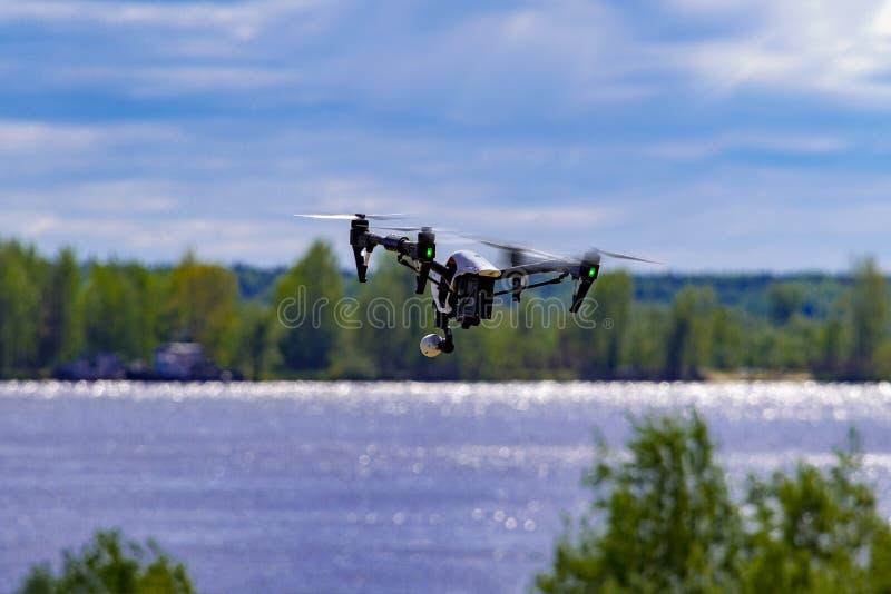 El abejón vuela sobre el río y el banco cerca de la ciudad foto de archivo