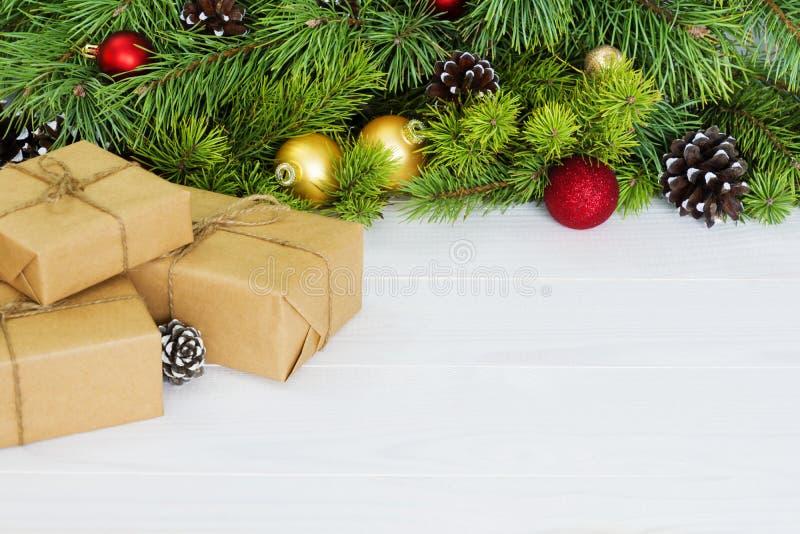 El abeto ramifica con los ornamentos - caja de regalo, conos acebo del pino y chucherías Fondo de la Navidad, espacio de la copia fotografía de archivo libre de regalías