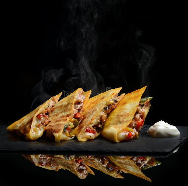 El abrigo mexicano del Quesadilla con crema agria de la pimienta dulce del pollo y la salsa caliente con vapor fuman imagenes de archivo