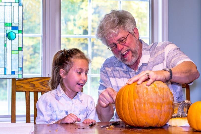 El abuelo ayuda a su nieta a tallar una calabaza imagen de archivo libre de regalías