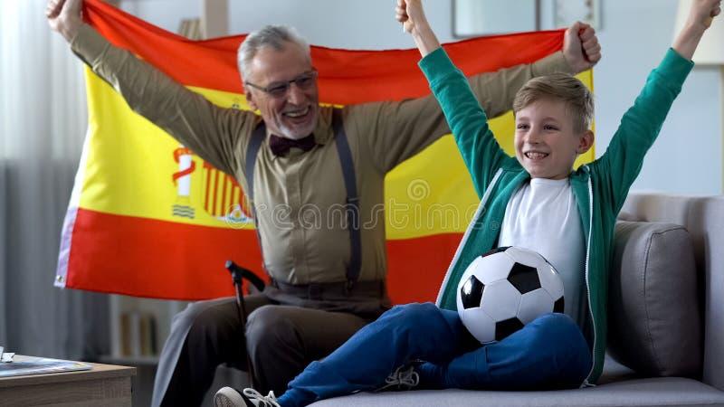 El abuelo que agita la bandera española, así como muchacho disfruta la victoria del equipo de fútbol foto de archivo libre de regalías