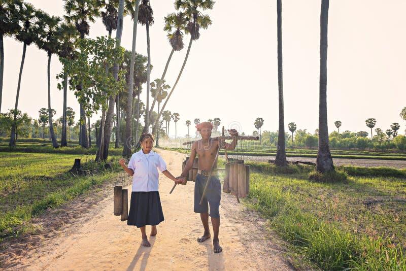 El abuelo que cuida para su nieta que camina detrás se dirige después de trabajo fotografía de archivo