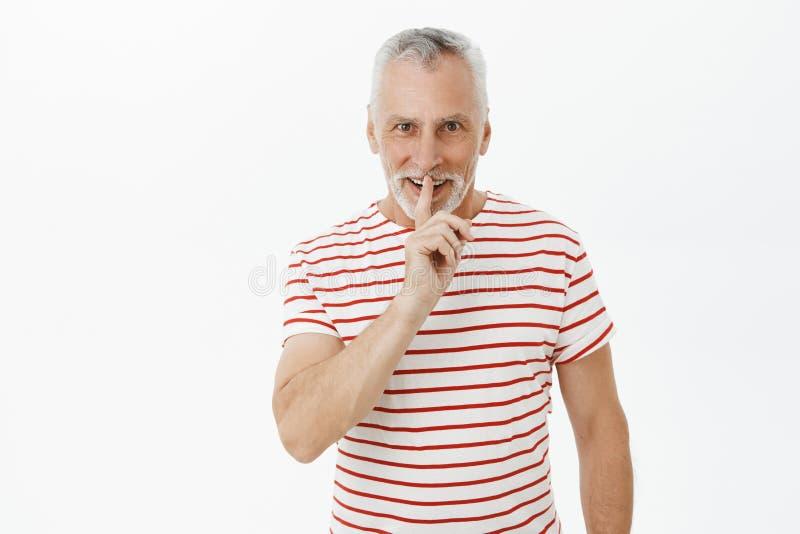 El abuelo que prepara la sorpresa para la esposa que dice shh la fabricación hace callar gesto con el dedo índice sobre la boca q fotos de archivo