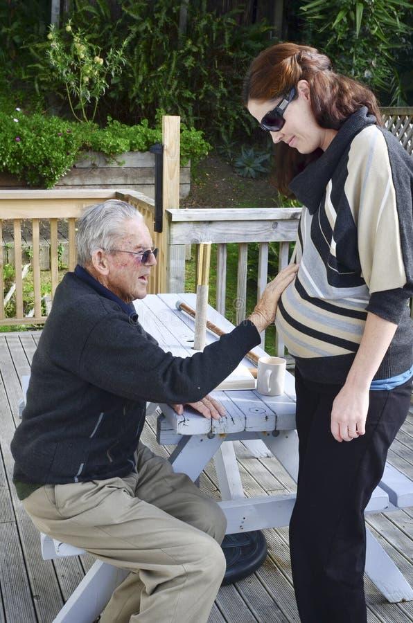 El abuelo se sostiene el abdomen embarazada de la nieta imagenes de archivo