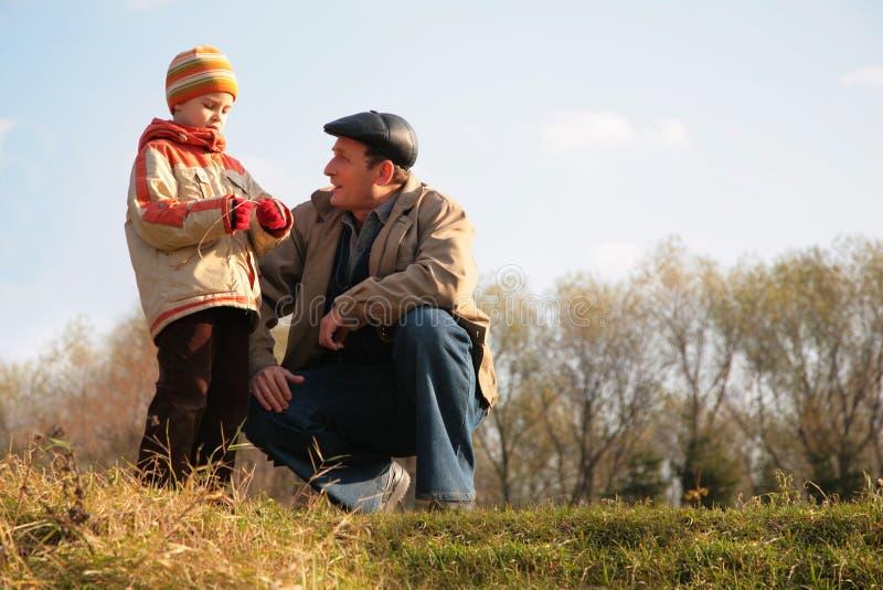El abuelo y el nieto se sientan en hillock fotos de archivo libres de regalías