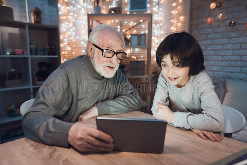 El abuelo y el nieto están mirando película en la tableta en la noche en casa imágenes de archivo libres de regalías